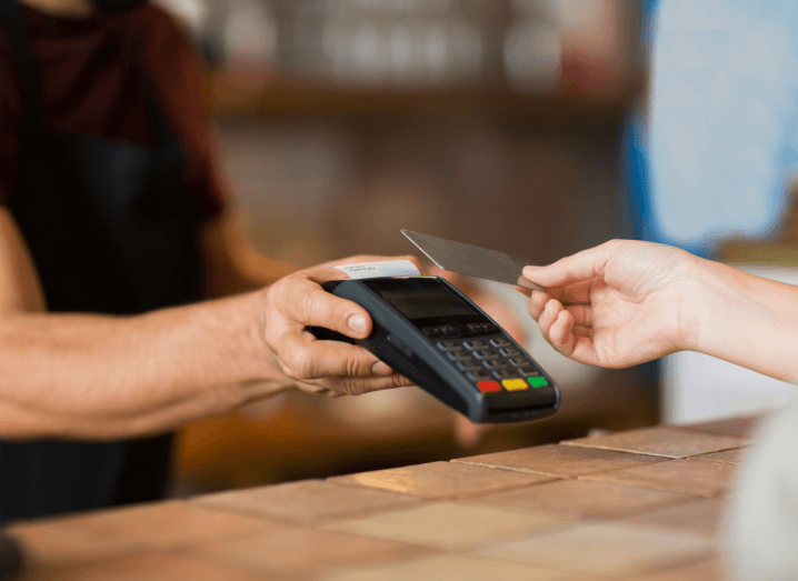 A person holding a card reader in a cafe or shop, and a customer extending their hand while holding a bank card.