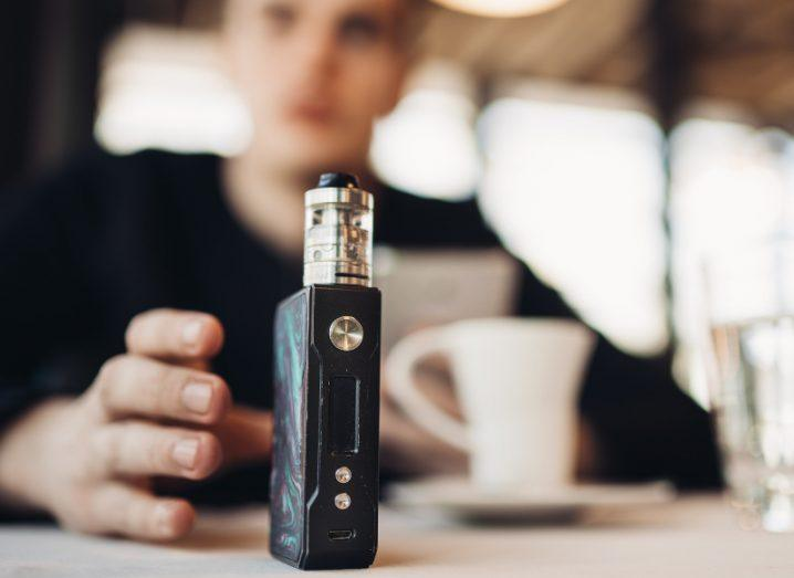 A man sitting with a coffee in a café reaches for an e-cigarette device in the foreground.