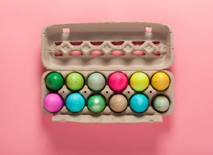 A batch of a dozen colourfully painted eggs in a carton on a soft pink background.