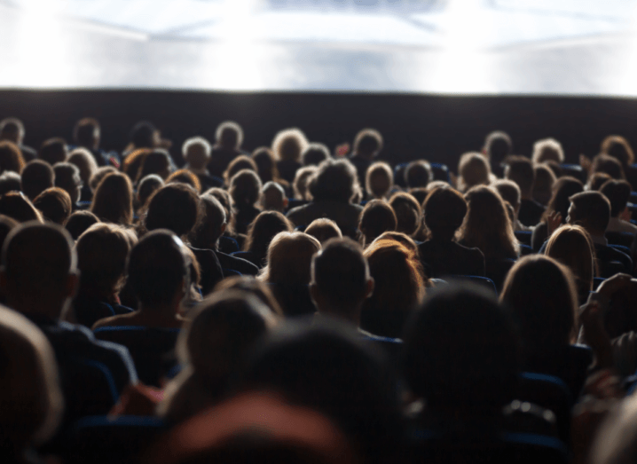 The view from the background of a movie theatre. There are rows and rows of heads sitting in red seats, staring up at a bright, white screen.