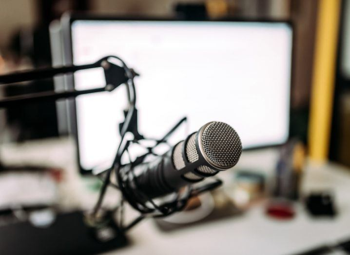 A home studio recording set-up with a microphone on an adjustable stand and an iMac set up in the background.