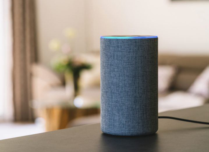 View of grey plush smart speaker sitting on dark wood table with blue band of light at top.