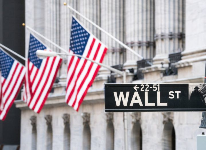 View of American flags hanging off a building and gently billowing in the wind with a Wall St street sign in the foreground.