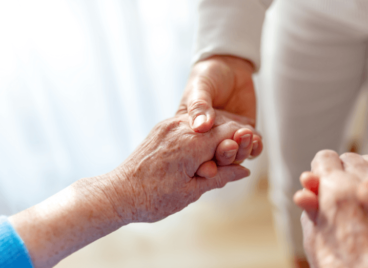 An adult holding the hands of an older person.