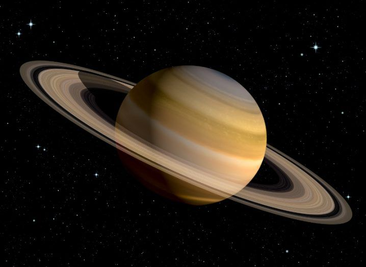 A view of a 3D rendering of Saturn with its prominent rings against a pitch black star-studded solar system backdrop.