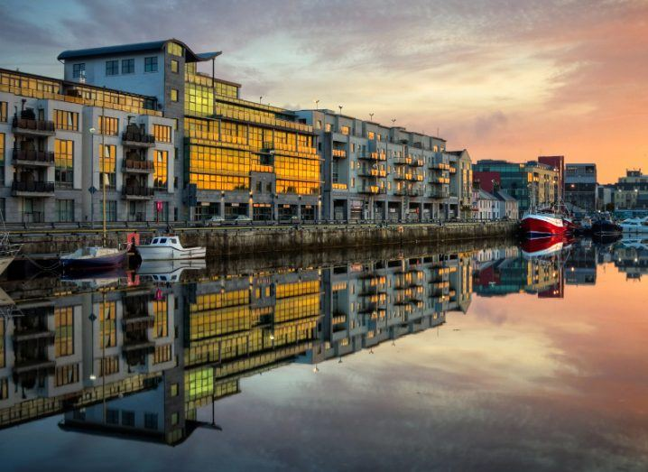 Morning view on Galway dock, boats and glass facades of buildings reflected on crystalline water.