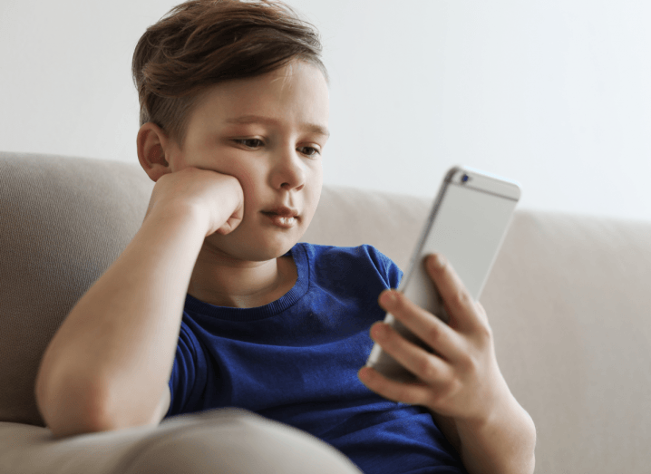 A little boy sitting on a sofa in a blue T-shirt, holding an iPhone 6 Plus. He has the phone in one hand and is resting his head on the other arm, which is propped up by the arm of the sofa. His expression is not particularly excited or engaged.