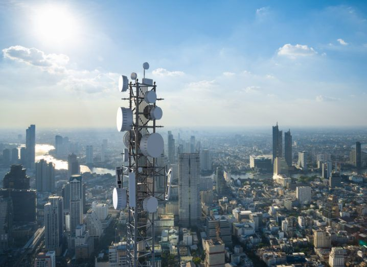 View of a telecommunication tower with 5G cellular network antenna against cityscape.