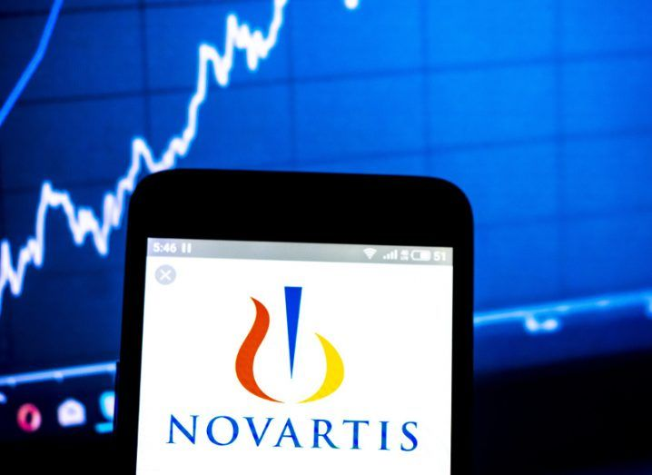 View of Novartis logo on smartphone on white background, with stock chart with climbing white line in the background.