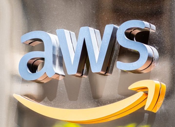 View of AWS logo of Amazon web services on metal wall bathed in sunlight.
