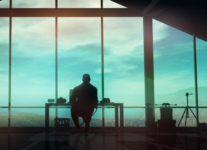 View of silhouette of man at desk doing work looking out window at coastline.