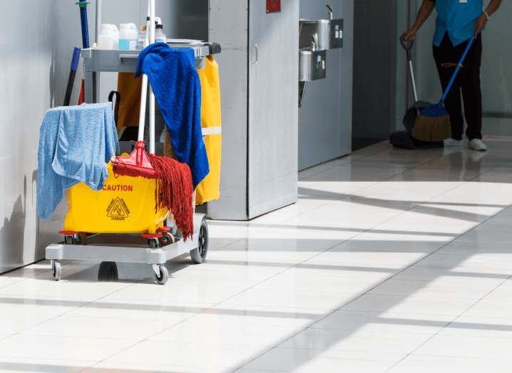 A bright corridor with a trolley full of cleaning supplies including cloths, wet floor signs, cleaning products and mops. In the background, a cleaner is vacuuming the floor.