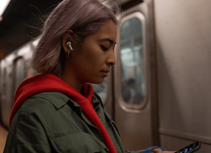 A woman with lilac hair stands in front of a subway train passing by, wearing an orange hoodie and a green jacket over it. She has the white AirPods Pro in her ear.