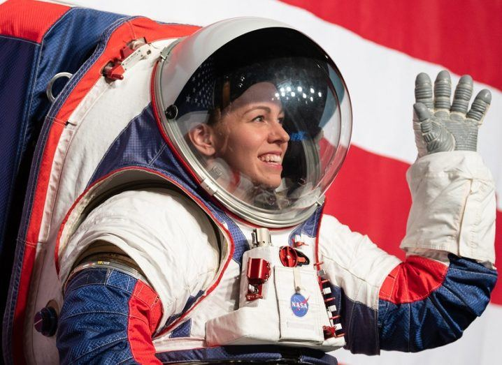NASA spacesuit engineer Kristine Davis wearing the new spacesuit, smiling and waving.