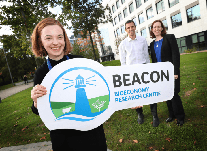 "A young woman with short, red hair, wearing a black dress, holds a large sign that reads ""Beacon Bioeconomy Research Centre"". Behind her is an older man and woman. The man is wearing a white shirt and the woman is wearing a blue top and black blazer. They are standing outside in front of a white building in front of autumn leaves."