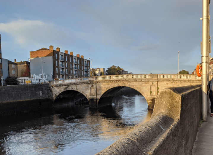 A blue sky over the Liffey. There is a concrete wall beside the river and further ahead in the picture, there is a stone bridge crossing the river. To the left, on the other side of the bridge there is a red brick building with the gable end covered in graffiti.