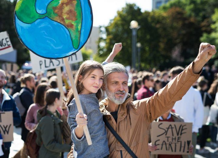 Young child holding a sign during a climate protest held up by a man with a white beard and brown jacket.