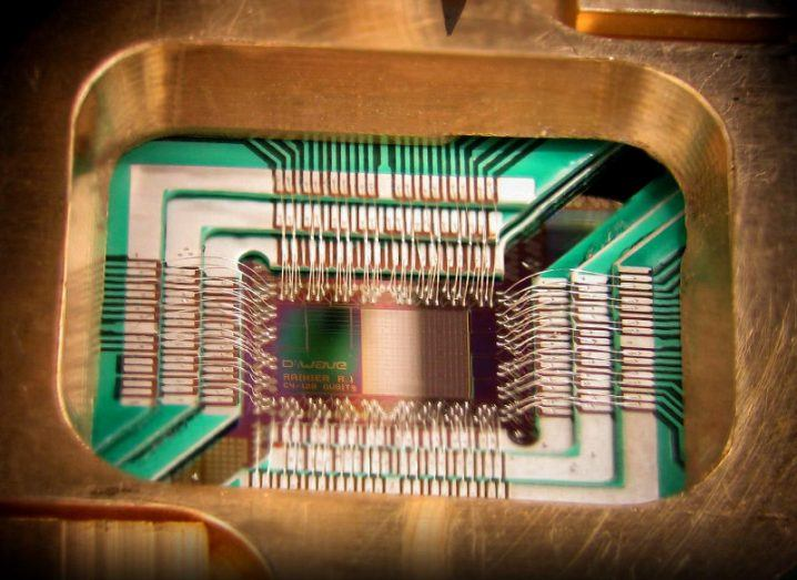 Close-up view of a chip labelled 'D-Wave Rainier R.1 C4/128 qubits' mounted inside gold casing.