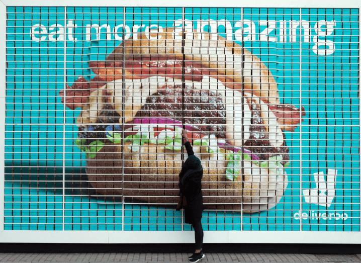 A person standing in front of a large Deliveroo billboard, wearing black jeans and a black coat. They are on their tippy toes reaching at a burger displayed on the billboard.
