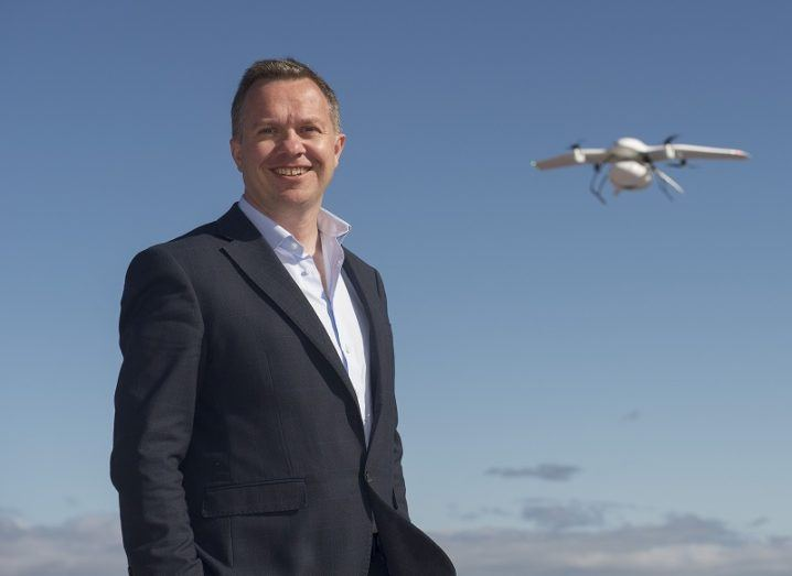 Prof Derek O'Keeffe smiling with a drone hovering in a blue sky background.