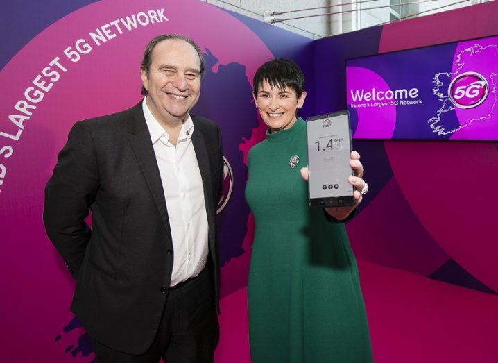 Xavier Niel and Eir CEO Carolann Lennon smiling and holding a 5G phone at the network launch event.