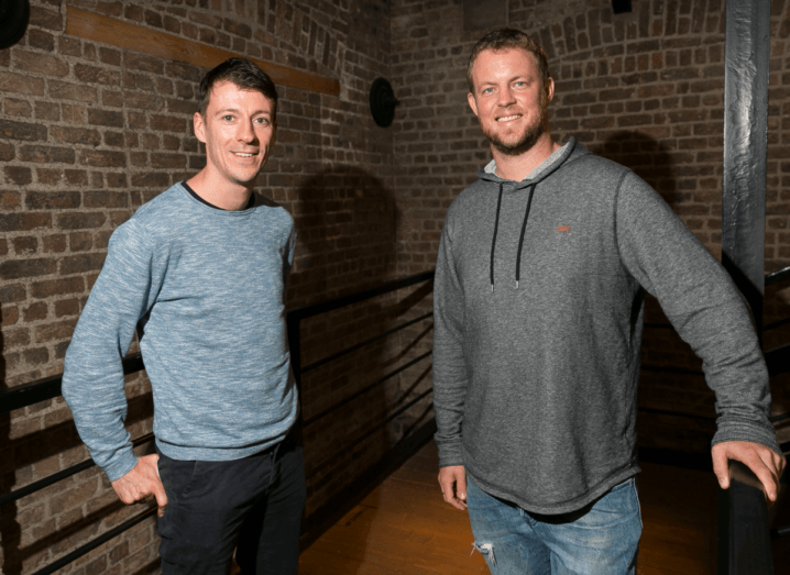 A man in a blue jumper standing with his hands in the pockets of his black jeans, who has black hair, standing beside another man in a grey hoodie and blue jeans. The man on the right has auburn hair. They are standing in a stairwell in front of an exposed brick wall.