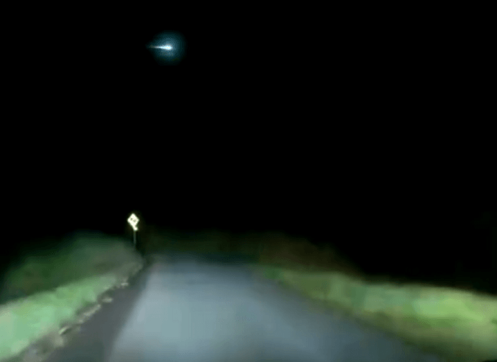 Dashcam screenshot of a fireball in the night's sky on a dark country road.