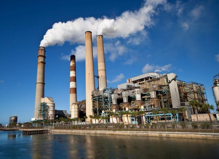 Power plant with smokestacks emitting greenhouse gases.