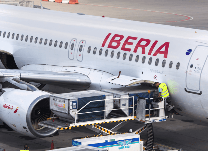An airline maintenance working in a high-vis vest standing on a platform beside a plane with the Iberia logo emblazoned on the side in red ink.
