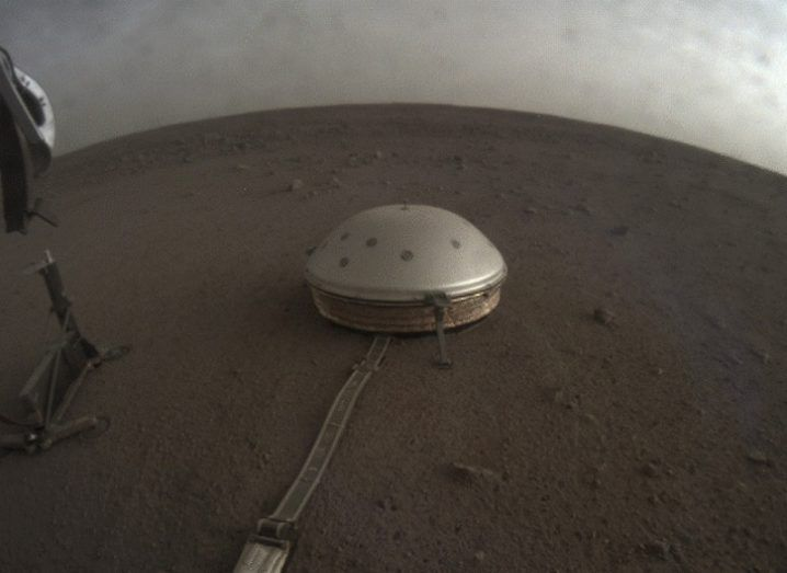 The InSight lander's dome-covered seismometer on Mars against an orange sky.