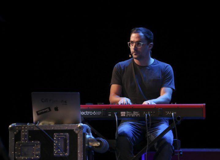 View of man on stage with glasses sitting at keyboard piano playing against black background.