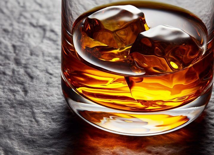 Tumbler glass filled with ice and Irish whiskey on a stone table.