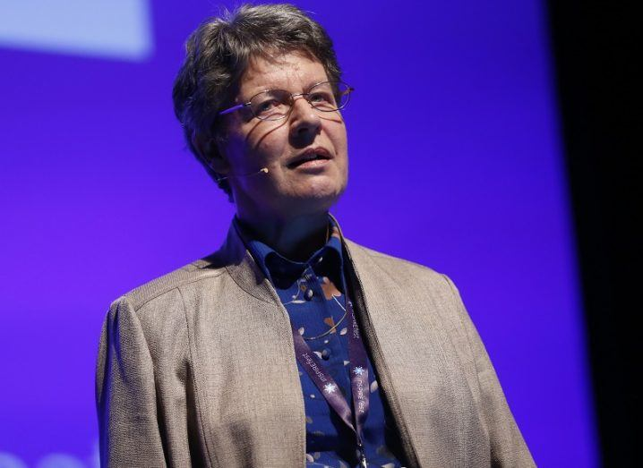 Jocelyn Bell Burnell speaking on stage at Inspirefest 2015 in a beige jacket and purple shirt against a purple background.