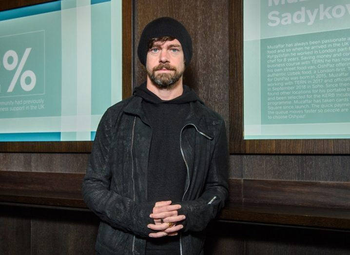 Jack Dorsey in a black leather jacket and beanie hat holding his hands together.