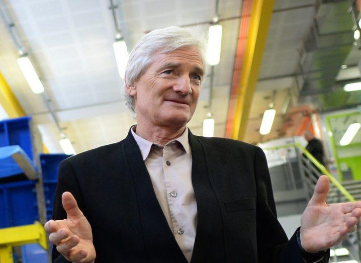 James Dyson wearing a black blazer and white shirt holding his hands out.