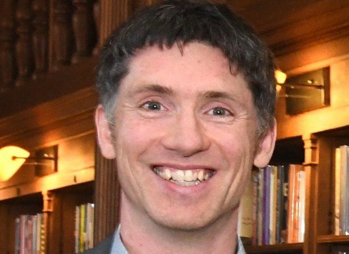 Headshot of Jamie Goggins smiling against a bookshelf background.