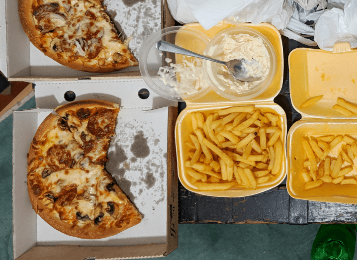 Two boxes of half eaten pizza beside a tray of chips and a tub of coleslaw.