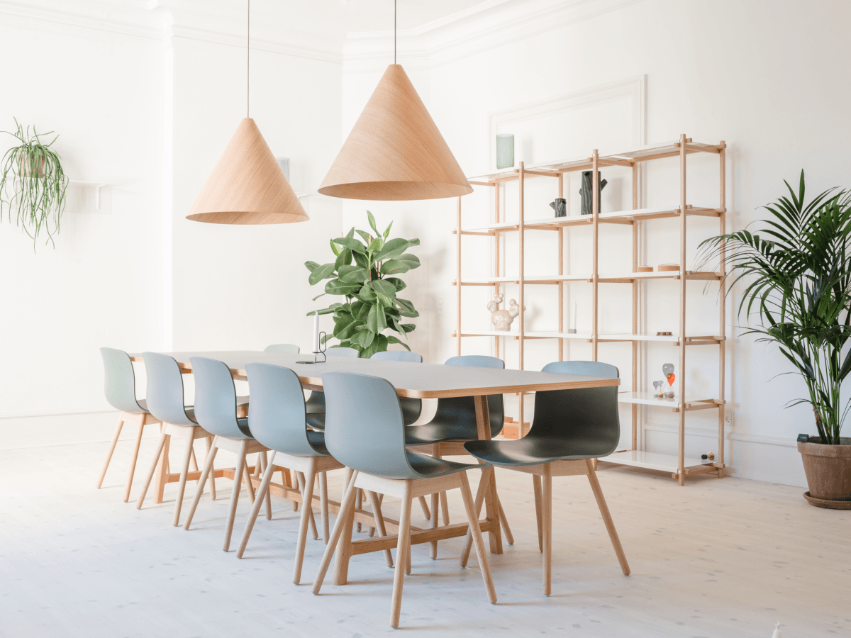Ten chairs tucked into a dining table underneath two large lampshades. The room is white and very bright, with a bookcase on the back wall and plants dotted around the room.