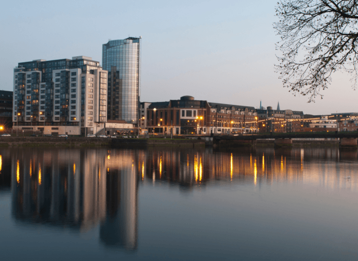 Tall buildings in front of a body of water in Limerick, at dusk. There are yellow lights in front of some of the buildings, which are reflected in the water.