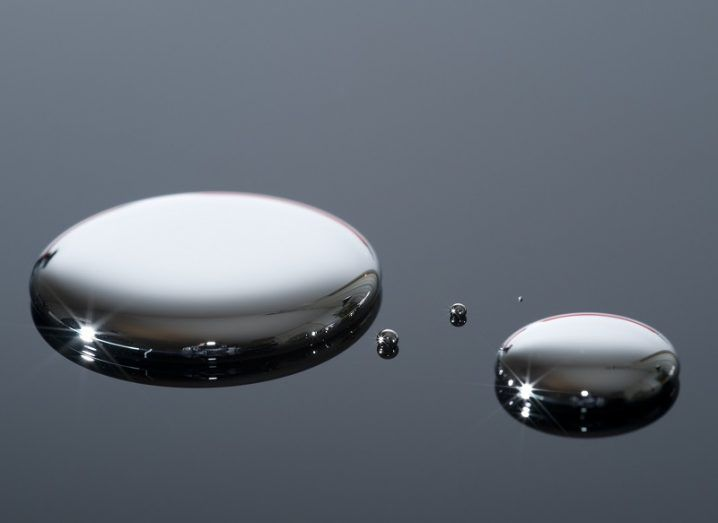 Two small puddles of liquid metal on a glass surface.