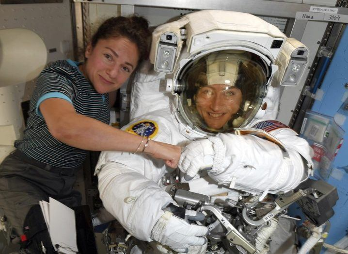 Christina Koch in her spacesuit and Jessica Meir fist bump and smile inside the International Space Station.