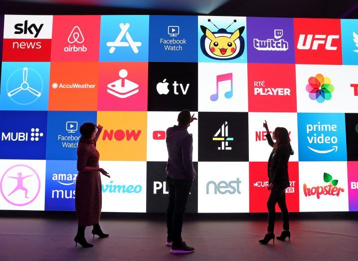 View of variety of streaming and tv apps on large screen with three people standing below pointing above to it.