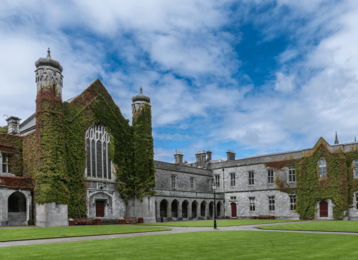 The historic quadrangle on NUI Galway's campus. A building covered in ivy with two towers under a blue sky with light, white clouds.