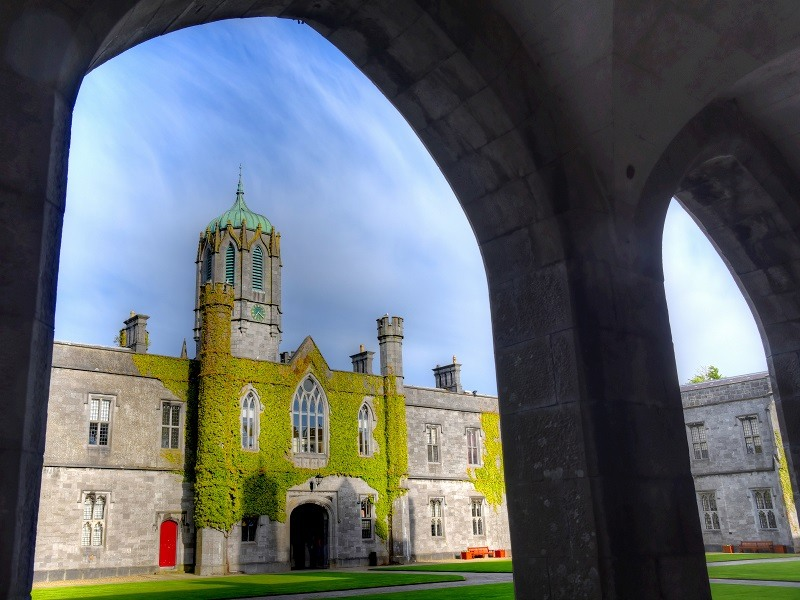 Shot from underneath an arch at NUI Galway against a blue sky.