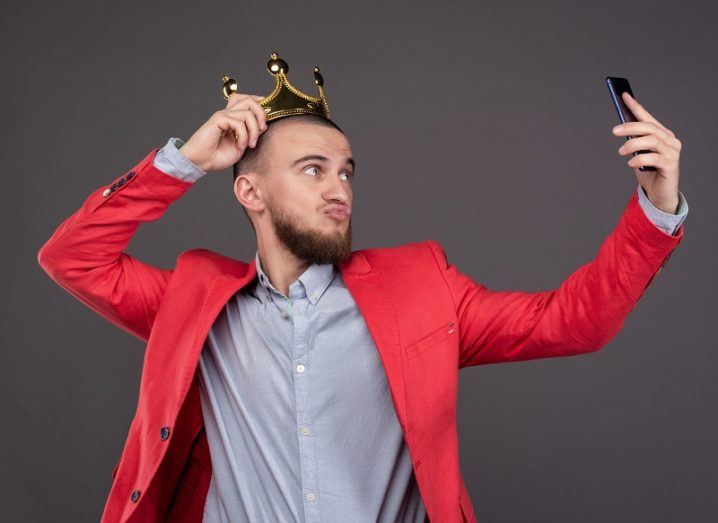 Young, bearded man in gold crown taking a selfie.