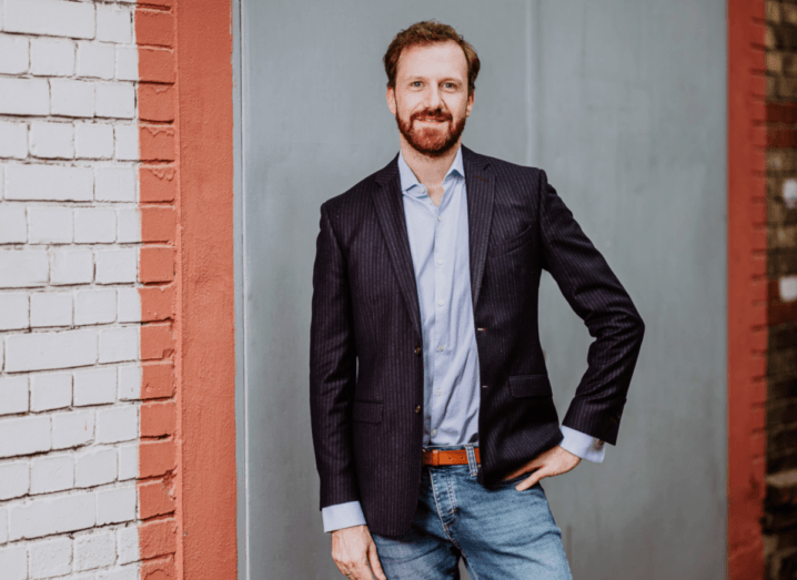A man in a pinstripe blazer stands with one hand on his waist smiling into the camera in front of a grey and red brick wall. He is wearing jeans and a brown belt, and a blue shirt under his blazer. He has a beard and short auburn hair.