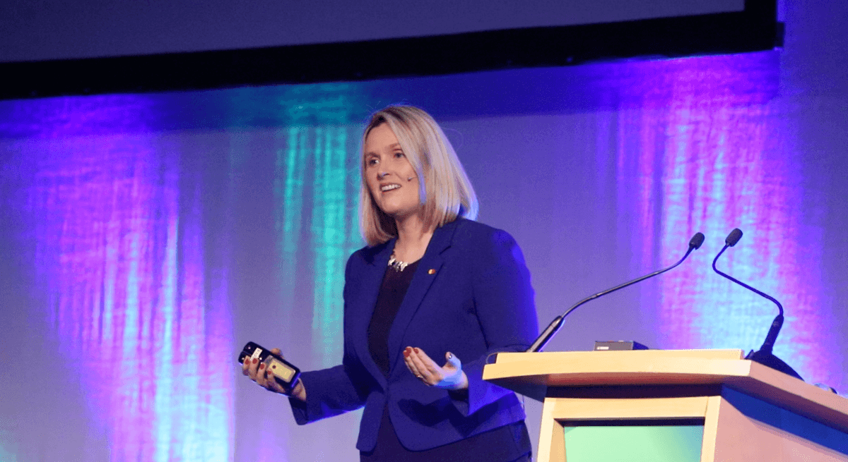 A professional woman in business attire is speaking on a stage by a podium against a purple background