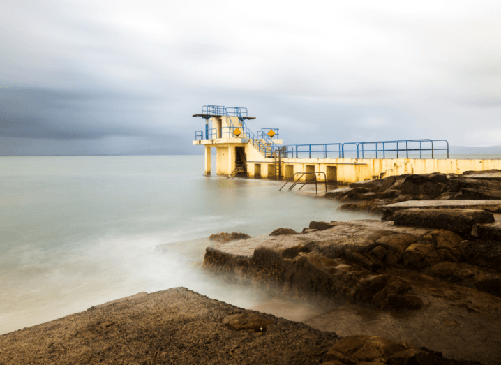 A yellow diving pier beside rocks and a body of water at Blackrock in Galway. There's a cloudy sky over the murky grey water.