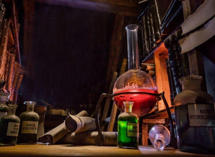 Old, dark lab with beakers filled with bright red and green liquid and a bunsen burner.