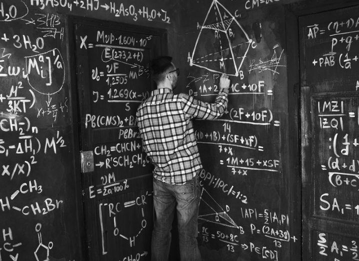 Black and white image of a scientist in checkered shirt at a large chalkboard covered in equations.